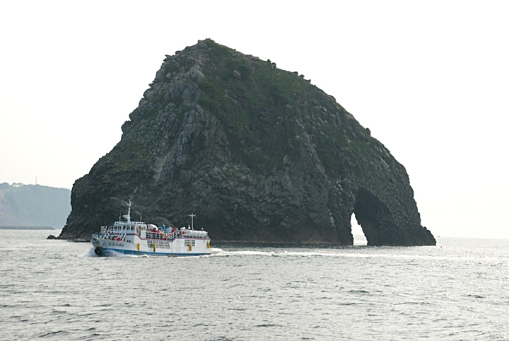 Impressive Elephant Rock off Ulleungdo's North shore dwarfs a nearby tour boat