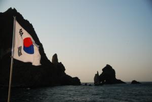 竹島 たけしま 獨島 독도 The Korean flag flies over Dokdo's East Islet with the West Islet in the background