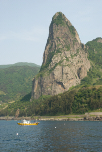 Song Got Mountain on the North side of Ulleungdo dwarfs a Korean fishing boat